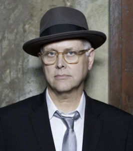 Photo of Eddie Muller wearins suit, glasses, and hat, very noir looking
