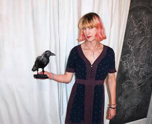 Author Charlie Jane Anders holding a fake blackbird