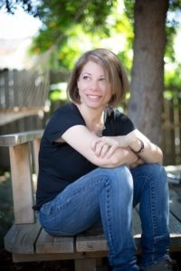 Photo of Jamie Mayer sitting and smiling