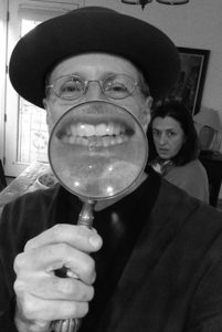 Photo of author David Gilmore holding up a magnifying glass to enlarge his smile
